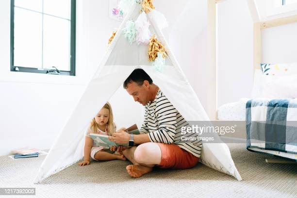 closeup portrait of a dad and child reading together in a child's room - teepee stock pictures, royalty-free photos & images