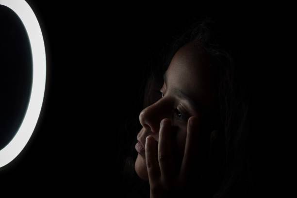Close-Up Portrait Of A Girl Looking At Halo Over Black Background