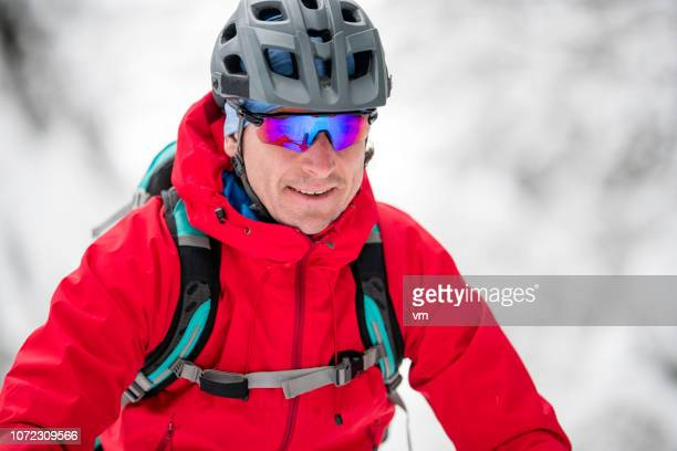 close-up portrait of a man cycling in the winter - cross country cycling stock pictures, royalty-free photos & images