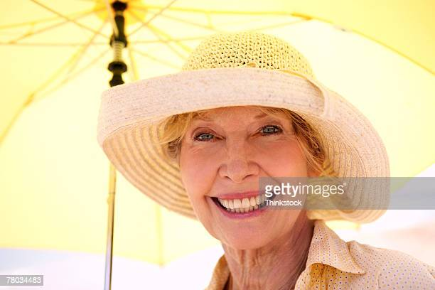 close-up portrait of a mature woman wearing  a floppy hat, smiling while holding a yellow umbrella - drooping stock photos and pictures