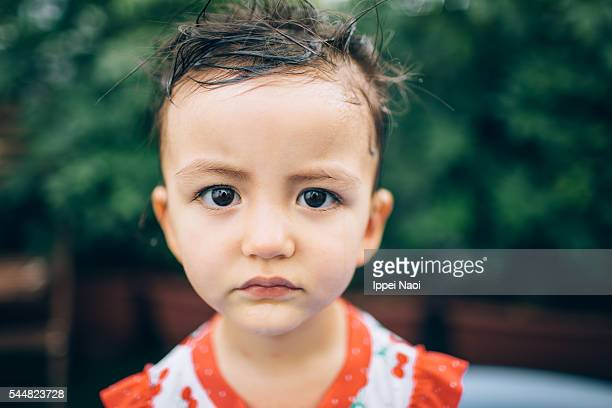 Close-up portrait of a moody mixed race toddler