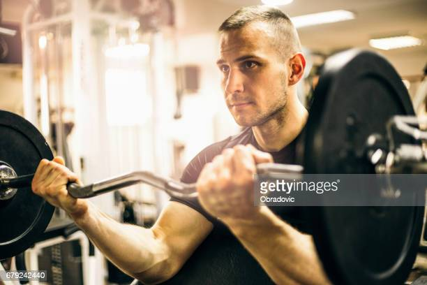 Closeup portrait of a muscular man workout with barbell in gym