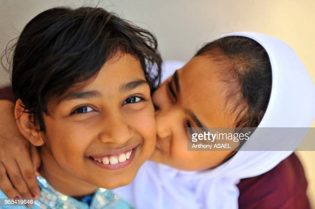 closeup portrait of a school girl kissing her friend in joy Muscat Oman