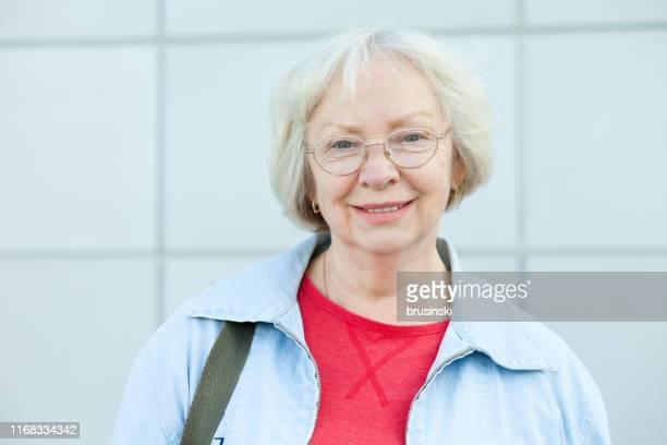 ritratto ravvicinato di una donna sorridente di 70 anni con gli occhiali - 65 69 anni foto e immagini stock