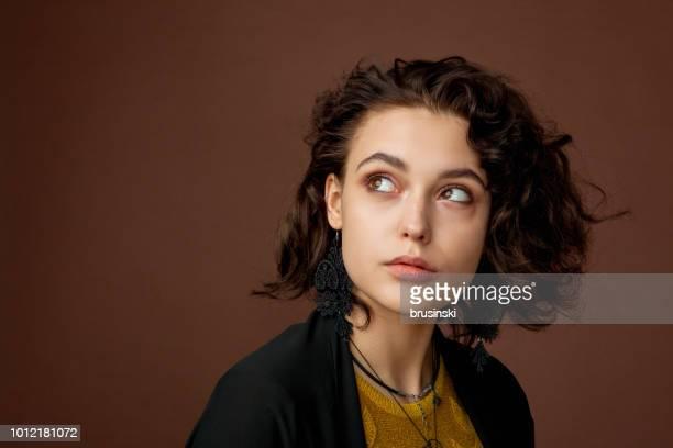 portrait de gros plan d'une belle jeune femme avec des cheveux bouclés en studio sur fond brun - lituanie photos et images de collection
