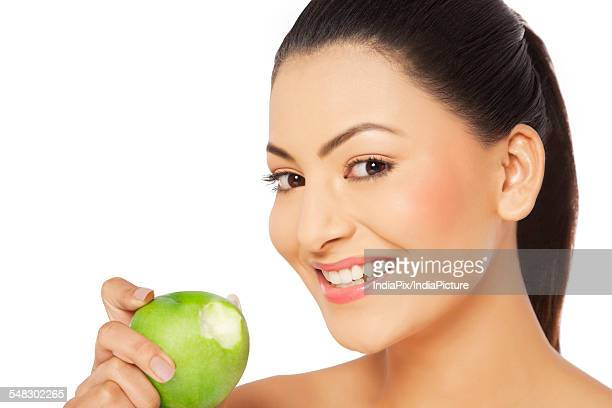 Close-up portrait of a young smiling woman holding green apple