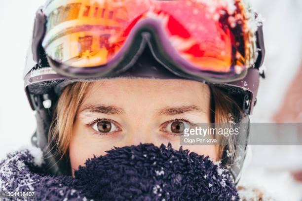 close-up portrait of a young woman wearing protective helmet and ski goggles during a snowfall. - événement sportif d'hiver photos et images de collection
