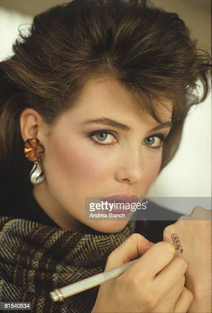Closeup portrait of American actress and model Kelly LeBrock as she writes a telephone number on her hand during a magazine photoshoot early 1980s