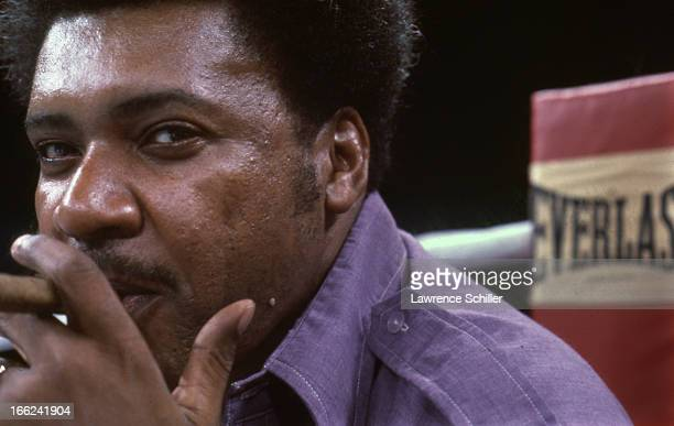 Closeup portrait of American boxing promoter Don King as he smokes a cigar in the ring the day before 'the Thrilla in Manila' at the Araneta Coliseum...
