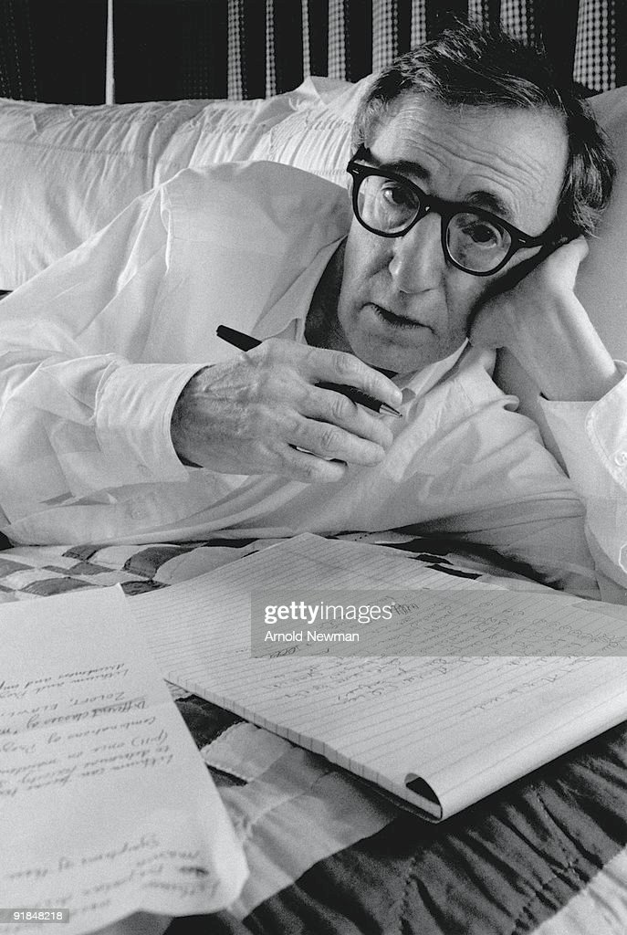 Close-up portrait of American film director and comedian Woody Allen lies on a bed and writes on a notepad, New York, New York, November 7, 1996.