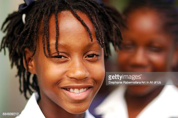 closeup portrait of an African schoolgirl with braided hair smiling with a friend in the background | Location Farmers Barbados