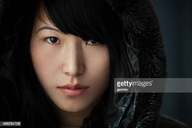 Close-up portrait of an Asian teenage girl looking at camera.