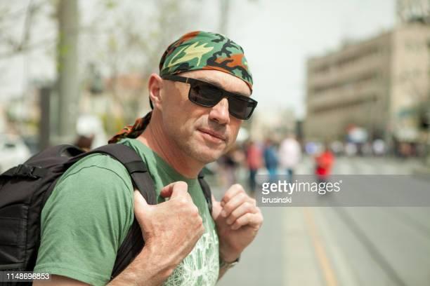 緑の t シャツとバンダナの魅力的な50歳の男性観光客のクローズアップポートレート - バンダナ ストックフォトと画像