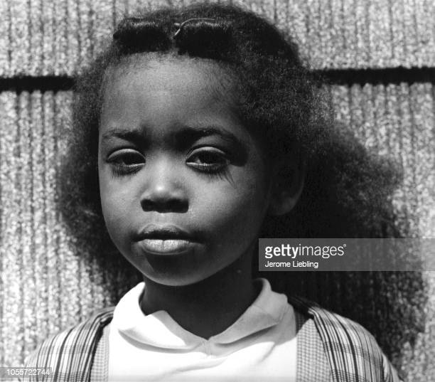Closeup portrait of an unidentified girl as she stands in front of a wall in the West Side neighborhood St Paul Minnesota 1962