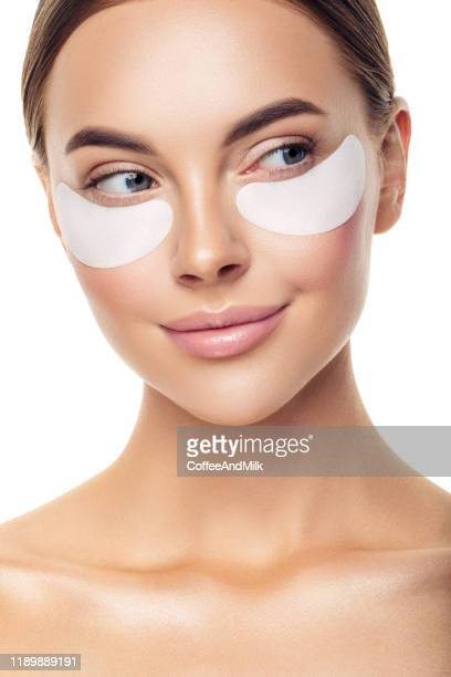 close-up portrait of attractive girl with naked shoulders applying patches on her face - padding stock pictures, royalty-free photos & images