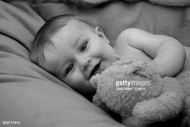 Close-Up Portrait Of Baby Boy Playing With Stuffed Toy On Bed
