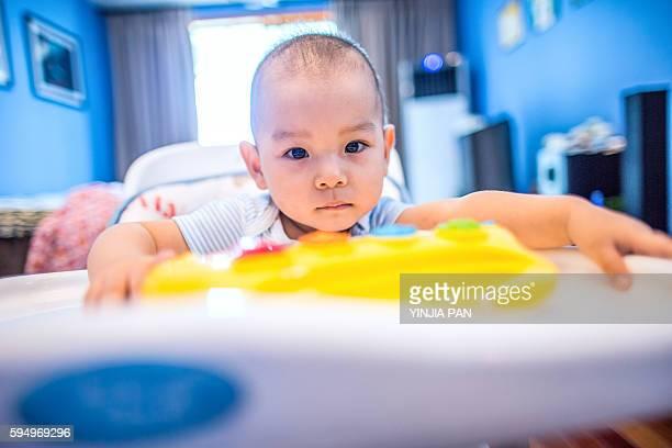 Close-up portrait of baby boy sitting in children's high chair