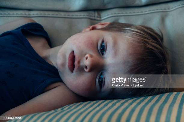 close-up portrait of baby lying on bed at home - forehead stock pictures, royalty-free photos & images