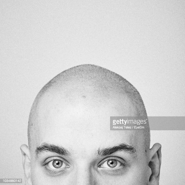 close-up portrait of bald man against white background - completamente calvo foto e immagini stock