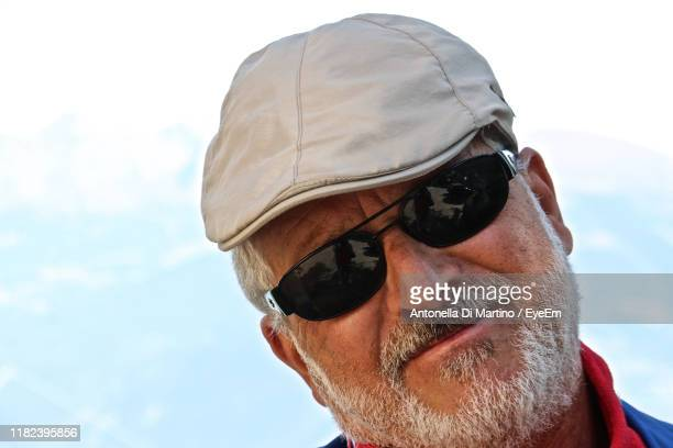 close-up portrait of bearded man in sunglasses against sky - antonella di martino foto e immagini stock