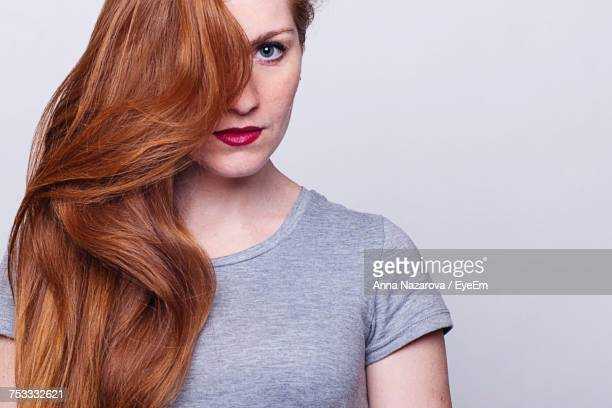 Close-Up Portrait Of Beautiful Woman Against White Background