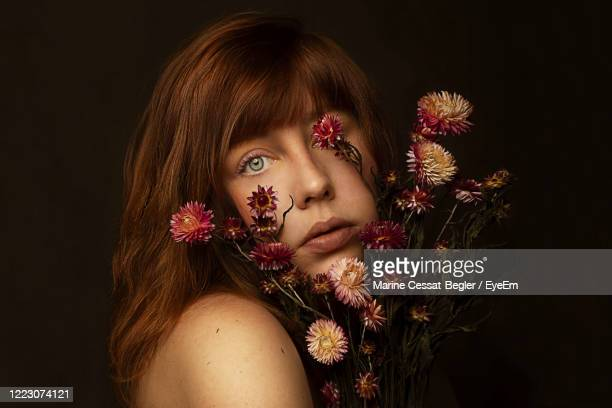 close-up portrait of beautiful woman holding flowers against black background - one young woman only stock pictures, royalty-free photos & images