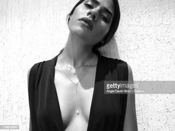 close-up portrait of beautiful woman standing by wall - cleavage close up stock photos and pictures