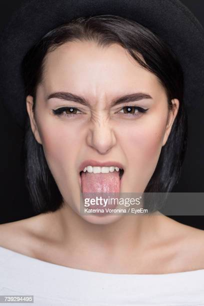close-up portrait of beautiful woman sticking out tongue against black background - tongue stock pictures, royalty-free photos & images
