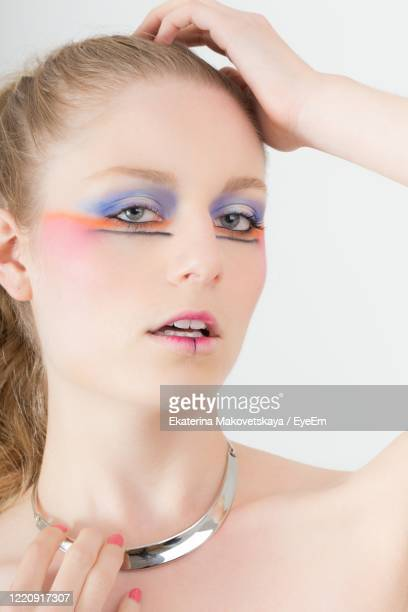 close-up portrait of beautiful woman with eye make-up against white background - girocollo collana foto e immagini stock