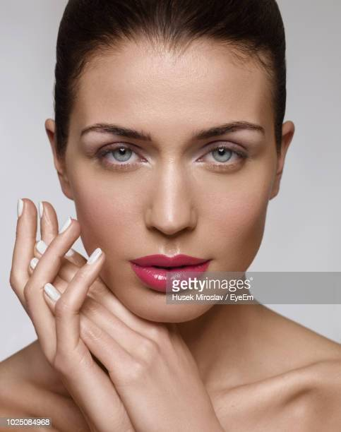 Close-Up Portrait Of Beautiful Woman With Make-Up Against White Background