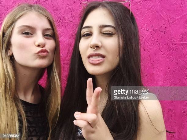 Close-Up Portrait Of Beautiful Young Friends Gesturing Against Magenta Wall