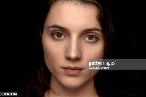 close-up portrait of beautiful young woman against black background - brown eyes stock pictures, royalty-free photos & images
