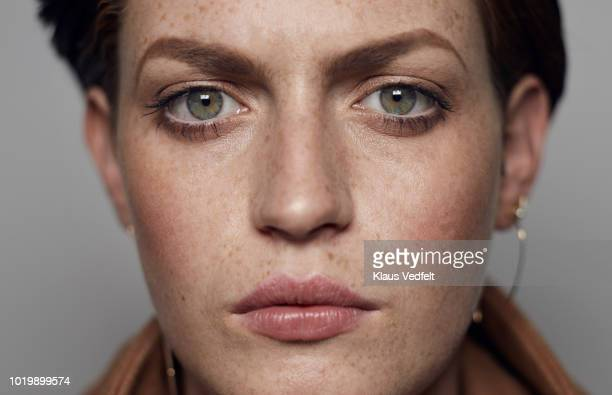 close-up portrait of beautiful young woman looking in camera, shot on studio - extreme close up stock pictures, royalty-free photos & images