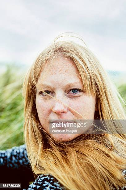 Close-up portrait of blond woman sitting on field