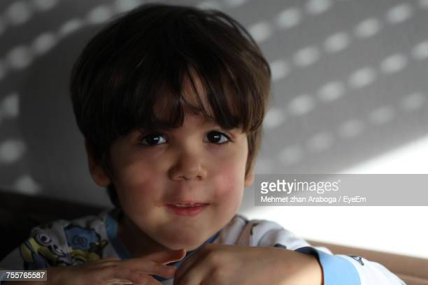 Close-Up Portrait Of Boy Against Wall At Home