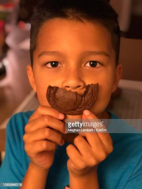 close-up portrait of boy holding cookie over mouth - meghan stock photos and pictures