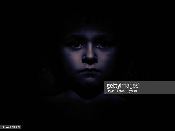 close-up portrait of boy over black background - fear stock pictures, royalty-free photos & images