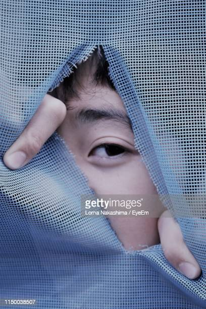 close-up portrait of boy peeking through textile - peeping holes ストックフォトと画像