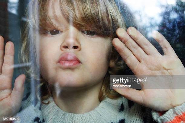 Close-up portrait of boy pressing lips and hands against window