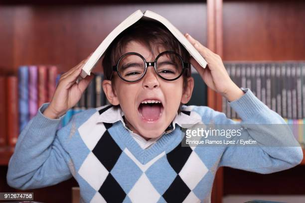 Close-Up Portrait Of Boy Screaming While Standing Against Bookshelf At Home