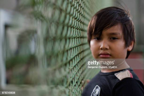 Close-Up Portrait Of Boy Standing By Chainlink Fence