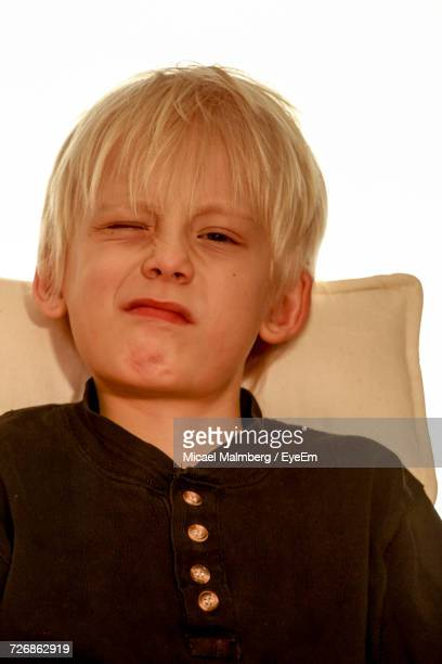 Close-Up Portrait Of Boy Winking While Sitting On Chair Against White Background