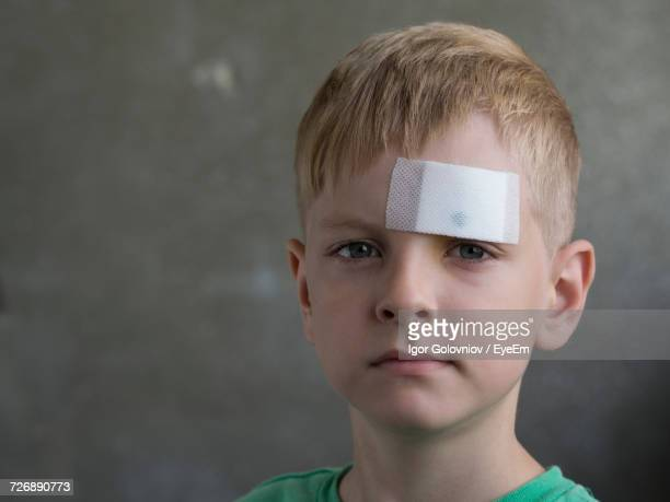 close-up portrait of boy with bandage on forehead against gray background - head bandage stock photos and pictures