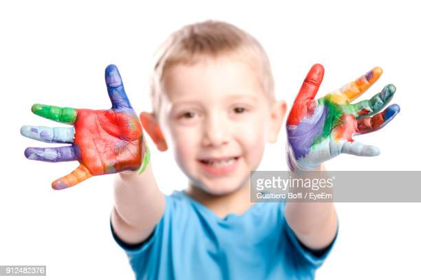 Close-Up Portrait Of Boy With Colorful Fingers Standing Against White Background