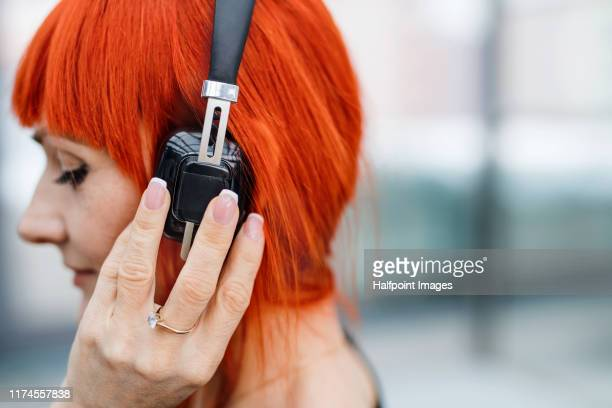 a close-up portrait of businesswoman with headphones in office building, listening to music. - dyed red hair stock pictures, royalty-free photos & images
