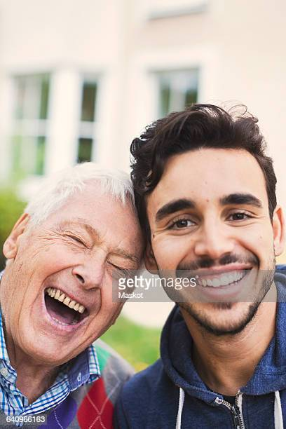 Close-up portrait of caretaker with happy senior man outside nursing home