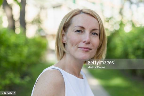 close-up portrait of confident smiling mature woman with short blond hair at park - sleeveless top stock photos and pictures