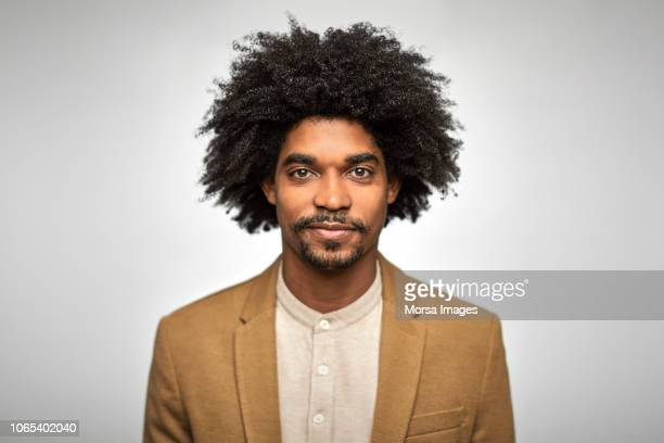 close-up portrait of confident young businessman - afro frisur stock-fotos und bilder