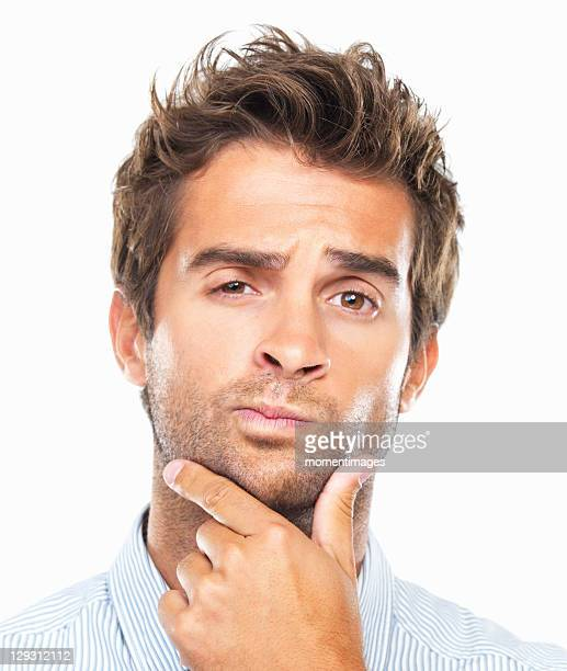 close-up portrait of confused business man with had on chin against white background - mano en la barbilla fotografías e imágenes de stock