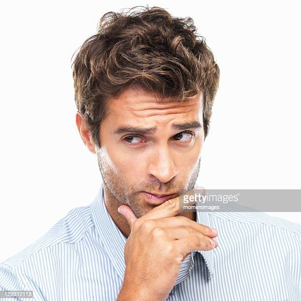 Close-up portrait of confused business man with had on chin against white background